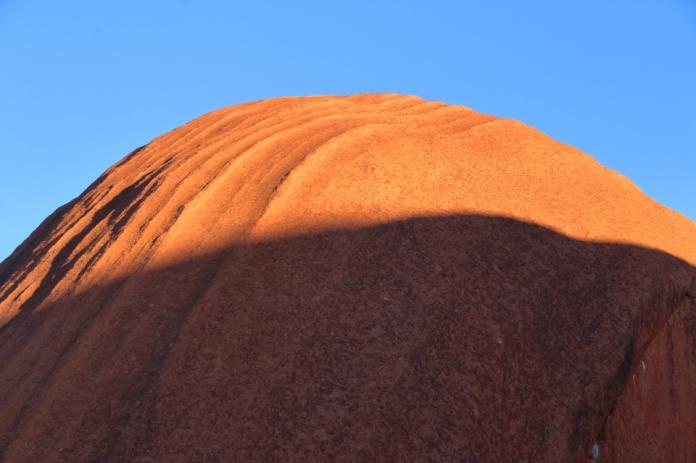 Le soleil commence à éclairer les pans de gré érodés d'Uluru (Photo Joris Bertrand)
